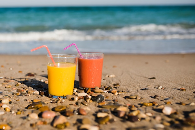 Two glasses of juice with drinking straw on sandy beach near the seashore