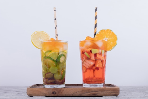Two glasses of juice with fruit slices on white wall.