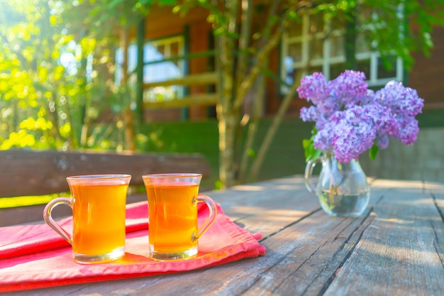 Two glasses of lemonade drink. a bouquet of beautiful lilacs in a glass vase stands on a wooden table. wooden cottage in the forest.