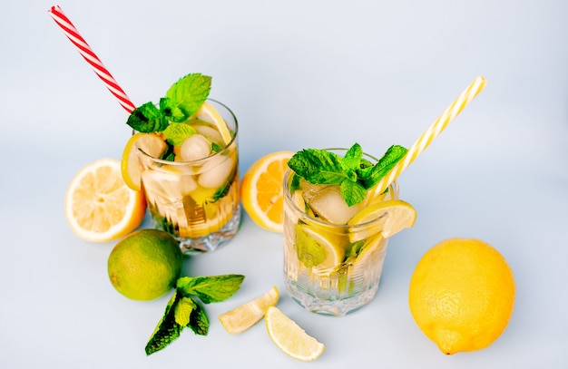 Two glasses of lemonade with lime, lemon and mint leaves, peach and ice