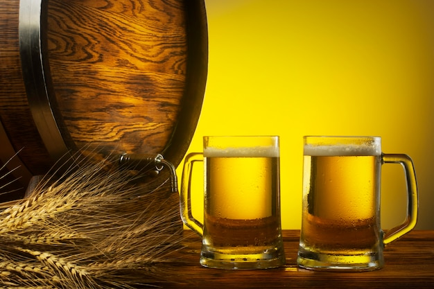 Two glasses of light beer an oak barrel and a sheaf of barley free space for an inscription
