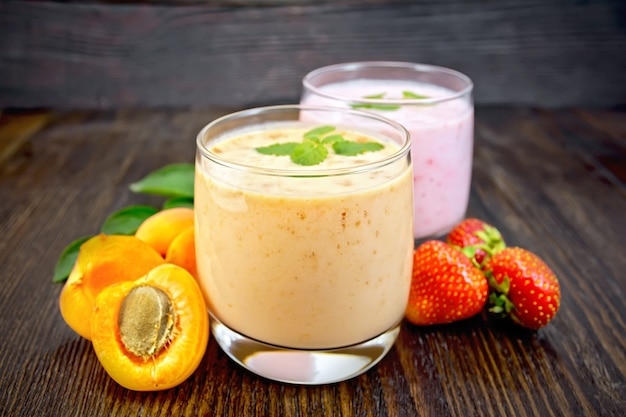 Two glasses of milkshake with apricots, strawberries and mint on a wooden plank background