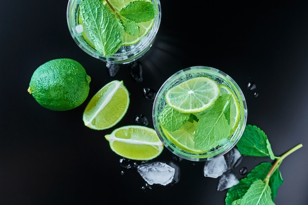 Two glasses of mint coctail with lime on dark, top view