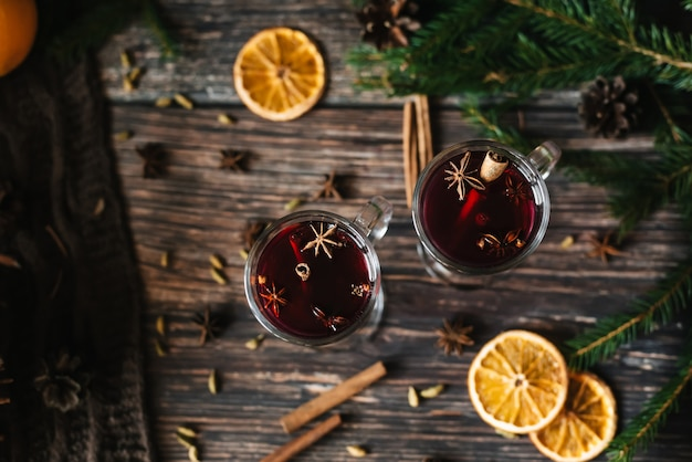 Two glasses of mulled wine with cinnamon, star anise, cardamom and orange