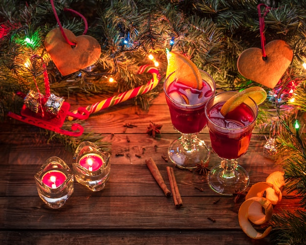 Two glasses of mulled wine with orange slices, candles and christmas tree with garland and toys