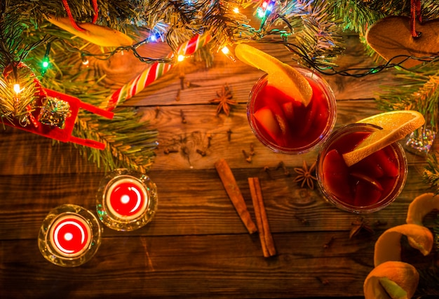 Two glasses of mulled wine with orange slices, candles and christmas tree with garland