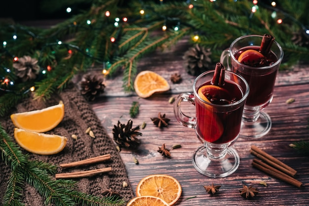 Two glasses of mulled wine with spices and orange slices on a wooden table. hot alcoholic drink