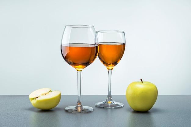 회색 표면에 과일 사과와 사과 주스 두 잔. 건강 식품 개념.