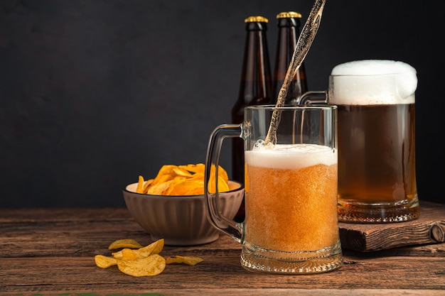 갈색 배경에 맥주, 칩, 맥주 병 두 잔. 측면 보기, 복사를 위한 공간입니다.