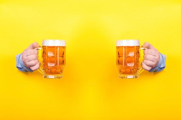 黄色の背景の上の手でビールを2杯