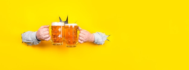 Два стакана пива в руках, чокнуться