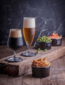フライドチキンピーナッツとポテトチップスの前菜を伴う素朴な木製のテーブルにビール2杯暗い大理石の壁
