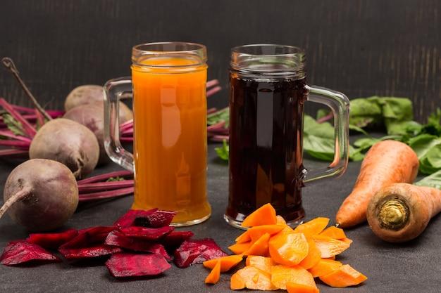 비트 뿌리와 당근 주스 두 잔. 비트 뿌리 채소와 껍질을 벗기지 않은 당근.