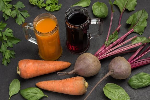 Два стакана свекольного и морковного сока. корнеплоды свеклы и моркови, петрушки и базилика. вид сверху. черный фон