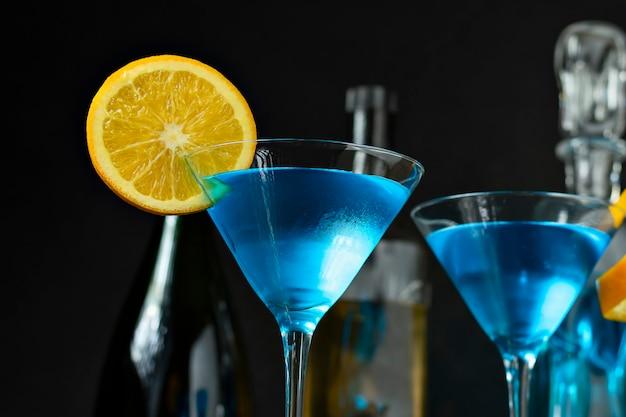 オレンジで飾られた青い飲み物2杯を間近で撮影