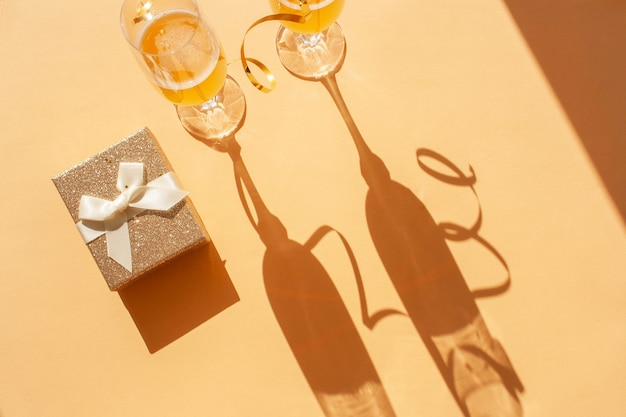 샴페인 두 잔과 금 선물 상자. 대조되는 그림자 추세. 휴일 장식