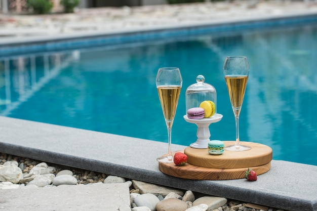 夏のホテルのプールの背景にシャンパン2杯とマカロンの花瓶。コピースペースのある側面図。水平方向。
