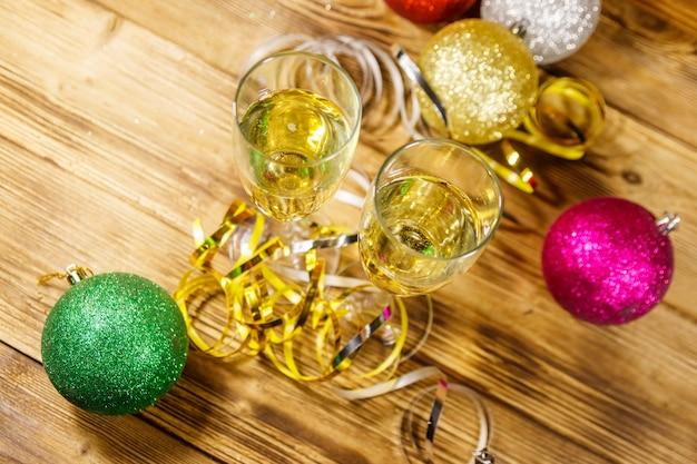 Два бокала шампанского и праздничные рождественские украшения на деревянном столе. вид сверху. празднование рождества и нового года