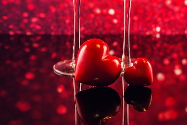 シャンパン2杯と背景に赤いハート型のボケ味の2つの赤いハート。ロマンチックなディナー。幸せなバレンタインデーのコンセプト。