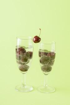 緑の背景に桜の飲み物で満たされたシャンパン2杯