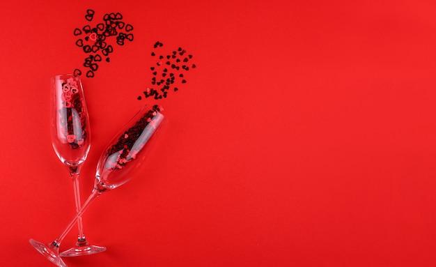 샴페인 두 잔 가득 심장 모양의 장식 조각 빨간색 배경 발렌타인 데이에.