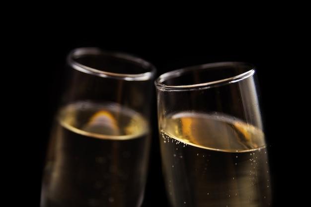 검은 배경에 샴페인 두 잔입니다. 축제 개념