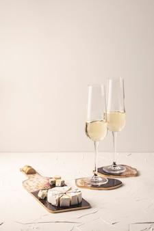 골드와 버건디 컬러의 에폭시 수지로 만든 안경과 스낵을위한 우아한 컵 받침에 샴페인 두 잔.