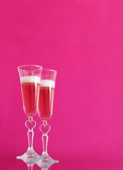 Два бокала шампанского на розовом фоне