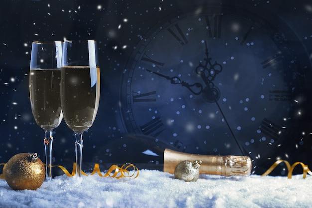 Два бокала шампанского с золотой лентой, звездой и шаром со снегом
