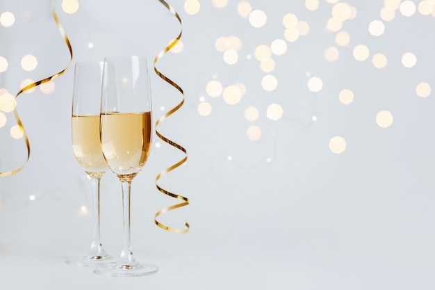 Два бокала шампанского с огнями и лентами на белом фоне праздника