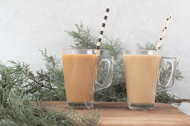 Два стакана кофе с соломкой на деревянной доске