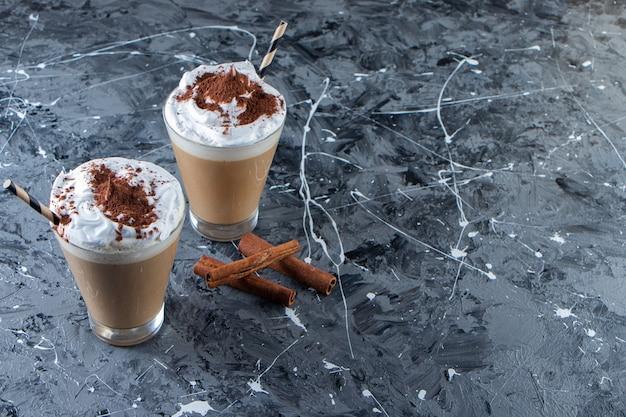 대리석 표면에 휘 핑된 크림과 함께 커피 두 잔.