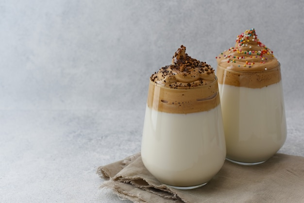 복사 공간와 밝은 배경에 dalgona 커피 두 잔. 푹신 푹신 크림 같은 휘핑 커피는 인스턴트 커피와 스프링 클로 장식되어 있습니다.