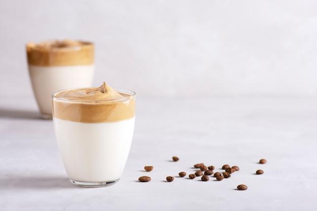 Dalgona 커피 두 잔은 회색 콘크리트 테이블에 서 있습니다.
