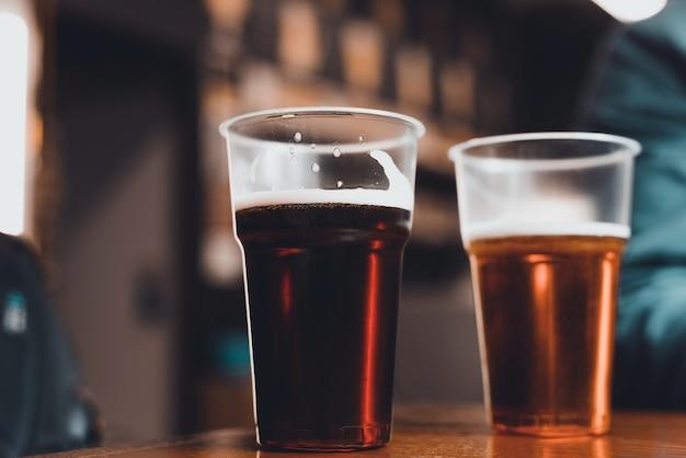 パブのテーブルの上に濃いビールと明るいビールを2杯、クローズアップ。セレクティブフォーカス、ぼかし