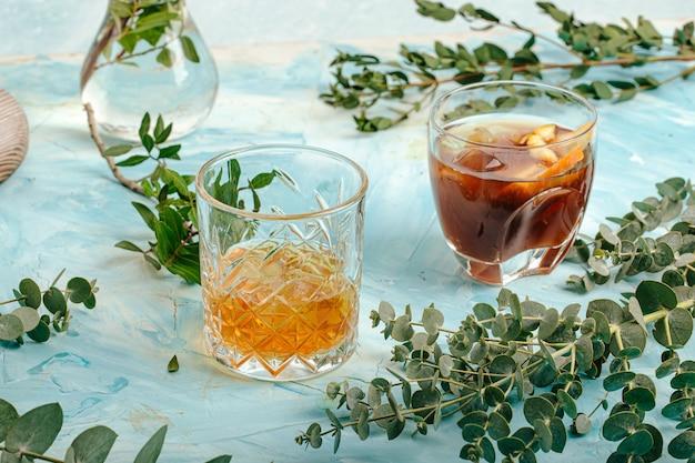 Два стакана разных алкогольных напитков на синем Premium Фотографии