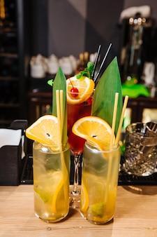 Два стакана свежих безалкогольных напитков из апельсина и лимона в стакане апельсиновых и лимонных дольок