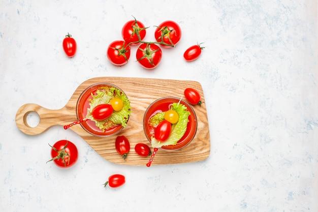 Два стакана свежего томатного сока и помидоров на серой бетонной поверхности