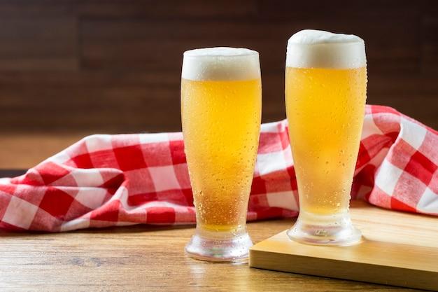 복사 공간이 나무 테이블에 격자 무늬 수건 옆에 거품 맥주 두 잔