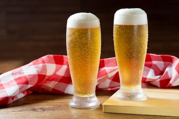 나무 테이블에 격자 무늬 수건에 대해 옆에 거품 맥주 두 잔