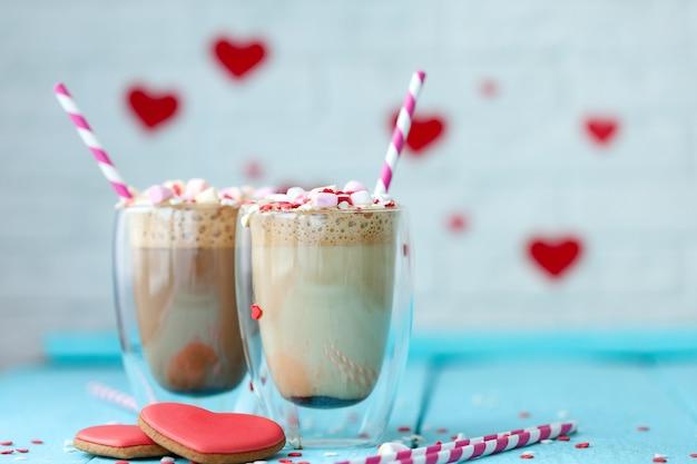 밝은 파란색 나무 배경에 마시멜로와 하트 모양 쿠키를 넣은 뜨거운 커피 또는 카푸치노 두 잔. 휴일 발렌타인 데이.