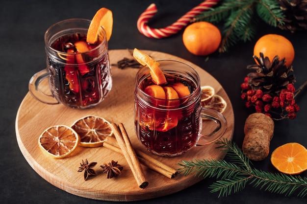 暗い背景にフルーツとスパイスを加えたホットホットワイン2杯。冬の温暖な休日の飲み物。