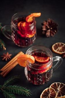 暗い背景にフルーツとスパイスとホットホットワイン2杯冬の休日の飲み物