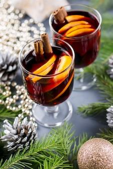 スパイスとスライスしたオレンジを添えたホットホットワイン2杯。キャンドルと装飾が施されたクリスマスドリンク。上面図