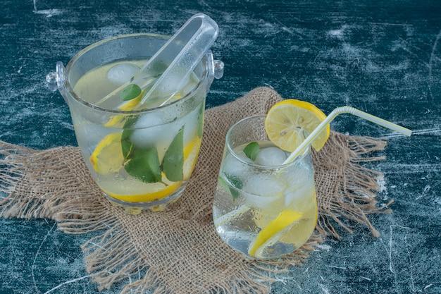 青い背景のタオルの上にアイスレモンドリンク2杯。高品質の写真