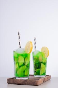 Два стакана сока с кусочками фруктов и свежими фруктами на белой стене.