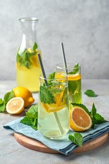 Два стакана лимонада и графин на сером фоне с лимонами. вертикальный вид. летний напиток.