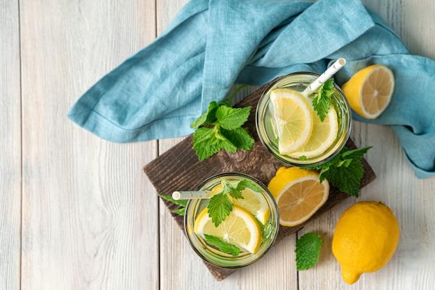 Два стакана лимонада, лимонов и мяты на светлом фоне. вид сверху, копия пространства.
