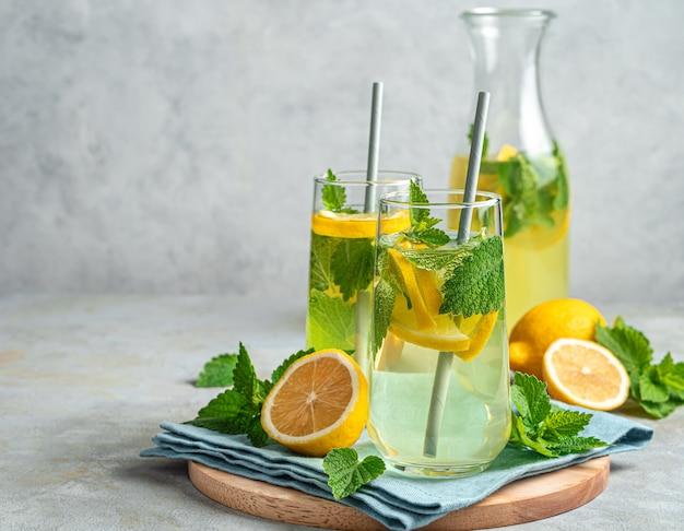 Два стакана лимонада или коктейль мохито на сером фоне. копирование пространства, вид сбоку.