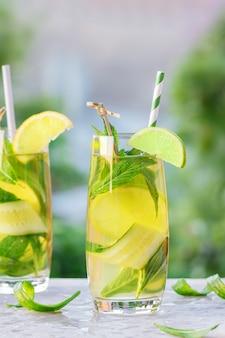 2杯のレモネードまたはモヒートカクテル、レモン、キュウリ、ミント、冷たいさわやかなドリンクまたはアイスペーパーストロー付き屋外飲料。夏のコンセプトです。冷たいデトックス水、コピースペース。